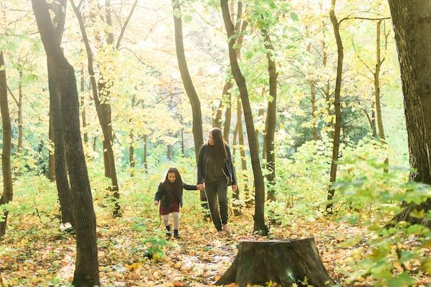 Młoda kobieta i jej córeczka spacerują po koncepcji samotnego rodzica i macierzyństwa w parku