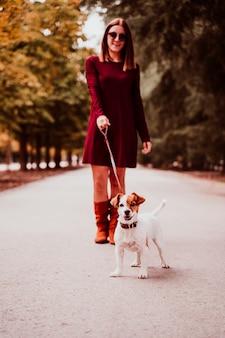 Młoda kobieta i jej jack russell są prześladowanym odprowadzenie w parku