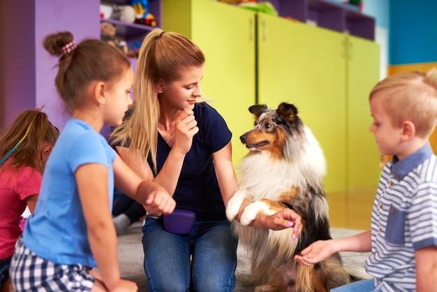 Młoda kobieta i jej pies bawią się z dziećmi podczas terapii