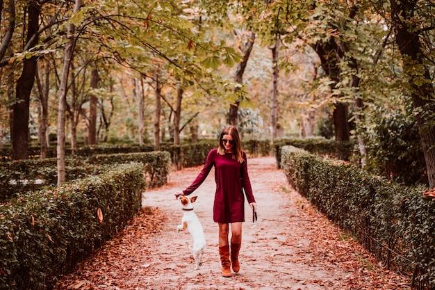 Młoda kobieta i jej śliczny jack russell są prześladowanym odprowadzenie w parku