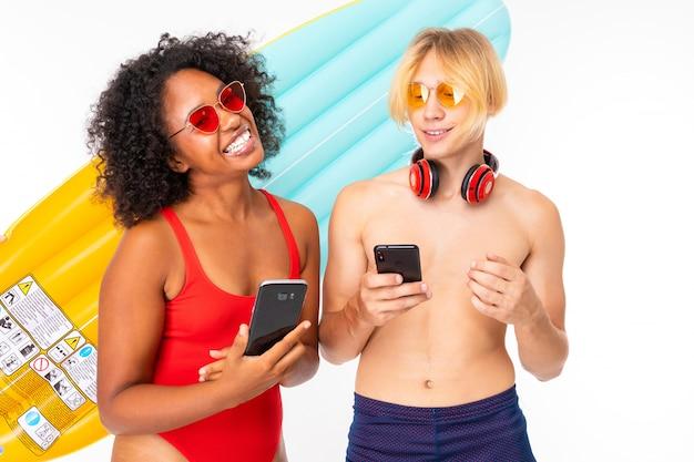 Młoda kobieta i kaukaski blondynka stoi w stroju kąpielowym z dużymi gumowymi materacami plażowymi, komunikuje się z przyjaciółmi przez telefony i uśmiecha się, na białym tle