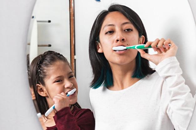 Młoda kobieta i mała dziewczynka myją zęby przed lustrem w łazience