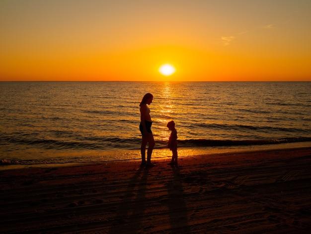 Młoda kobieta i mała dziewczynka stoją naprzeciw siebie nad brzegiem morza na tle zachodzącego słońca.
