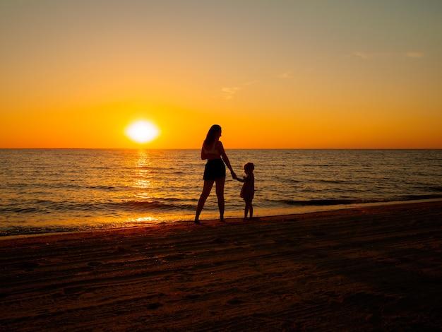 Młoda kobieta i mała dziewczynka trzymają się za ręce nad brzegiem morza na tle zachodzącego słońca.