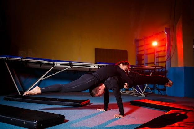 Młoda kobieta i mężczyzna gimnastycy wykonują ćwiczenia akrobatyczne na siłowni. zajęcia sportowe, zdrowy styl życia