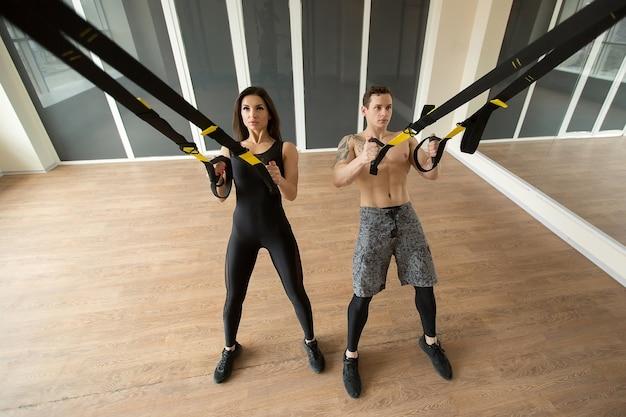 Młoda kobieta i mężczyzna trening pompek z paskami trx fitness na siłowni