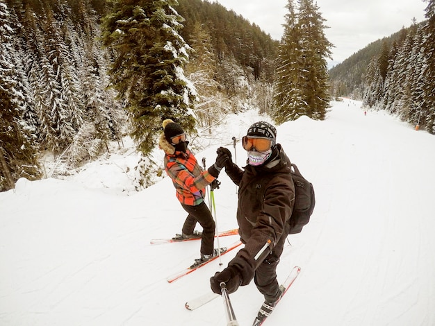 Młoda kobieta i mężczyzna trzymając się za ręce podczas jazdy na nartach w słoneczny dzień na wakacjach.