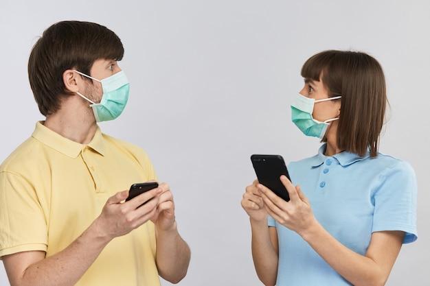 Młoda kobieta i mężczyzna w żółtych i niebieskich ubraniach, trzymając telefony i zaskakująco patrząc na siebie z przerażającymi wiadomościami na temat koronawirusa w internecie