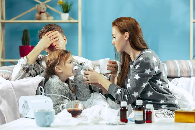 Młoda kobieta i mężczyzna z chorą córką w domu. leczenie w domu. walka z chorobą. opieka medyczna.