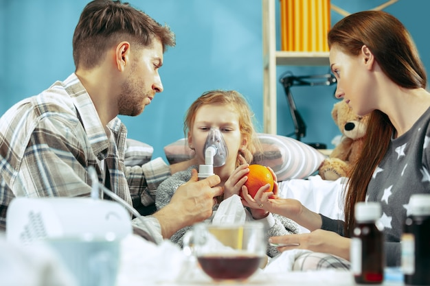 Młoda kobieta i mężczyzna z chorą córką w domu. leczenie w domu. walka z chorobą. opieka medyczna