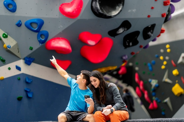 Młoda kobieta i mężczyzna za pomocą telefonu komórkowego w siłowni wspinaczkowej.