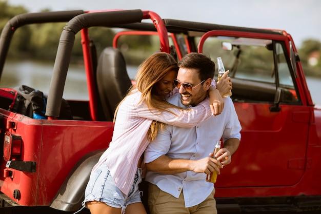 Młoda kobieta i mężczyzna zabawy na świeżym powietrzu w pobliżu czerwony samochód w letni dzień