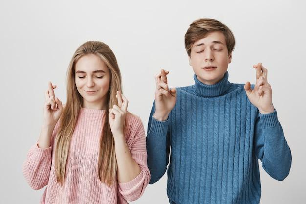Młoda kobieta i mężczyzna zamykają oczy i trzymają kciuki z nadzieją, oczekując ważnych wiadomości