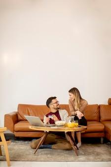 Młoda kobieta i młody mężczyzna za pomocą laptopa do płatności online, siedząc przy kanapie w domu