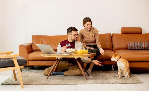 Młoda kobieta i młody mężczyzna za pomocą laptopa do płatności online, siedząc przy kanapie z psem shiba inu w domu