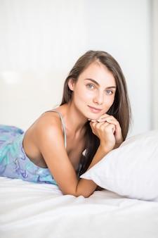 Młoda kobieta i ono uśmiecha się podczas gdy kłamający na łóżku w domu