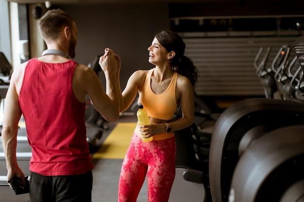 Młoda kobieta i osobisty trener odpoczywają na siłowni po treningu