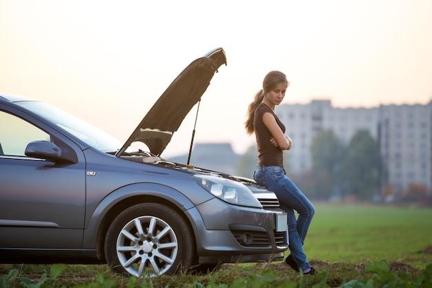 Młoda kobieta i samochód z pękniętą maską