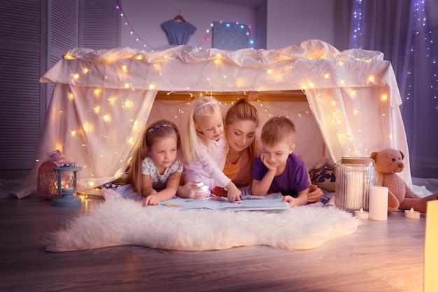 Młoda kobieta i słodkie dzieci czytają książkę w chacie w domu