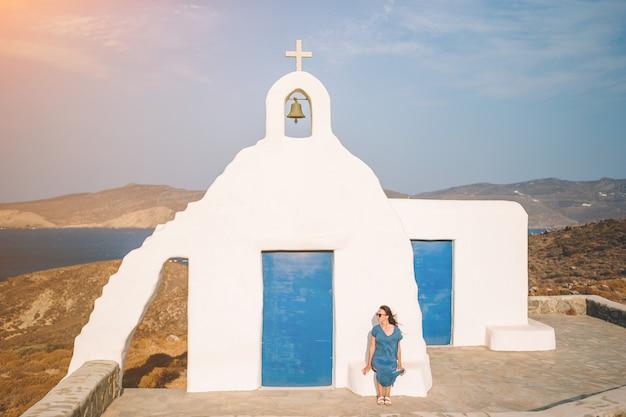 Młoda kobieta i tradycyjny biały kościół z dennym widokiem w mykonos wyspie, grecja