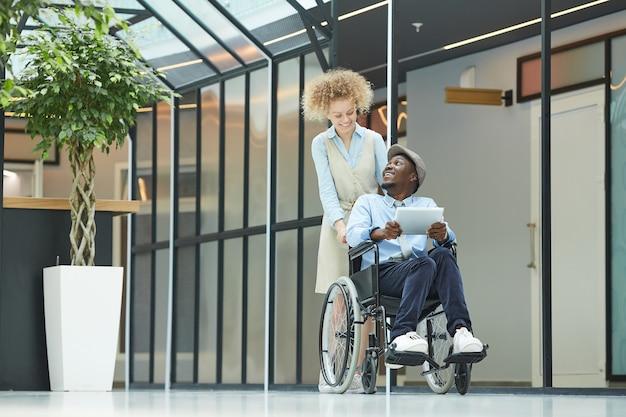 Młoda kobieta idąc korytarzem z niepełnosprawnym mężczyzną na wózku inwalidzkim on przy użyciu komputera typu tablet