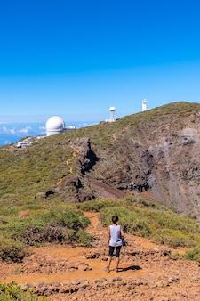 Młoda kobieta idąca obok teleskopów parku narodowego roque de los muchachos na szczycie caldera de taburiente, la palma, wyspy kanaryjskie. hiszpania