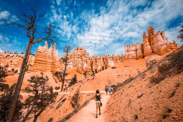 Młoda kobieta idąca wzdłuż gigantycznych, zerodowanych kamieni na queens garden trail