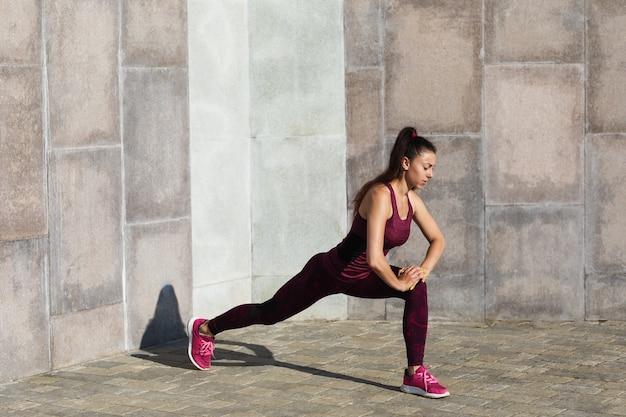 Młoda kobieta idzie do sportu w słoneczny letni poranek na świeżym powietrzu