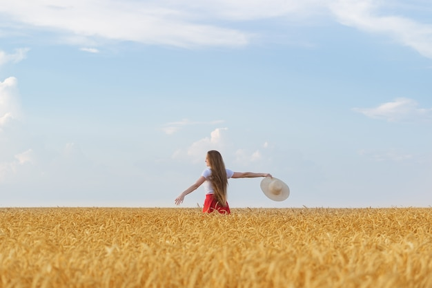 Młoda kobieta idzie przez pole pszenicy z kapeluszem w ręce i ciesząc się słoneczny dzień. wolność i odpoczynek
