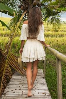 Młoda kobieta idzie przez stary drewniany most na wsi