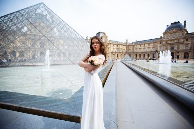 Młoda kobieta idzie w białej koronkowej sukience