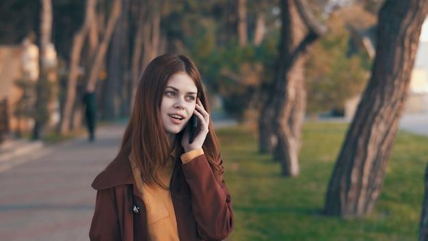 Młoda kobieta idzie w jesiennym parku w płaszczu przeciwdeszczowym