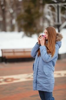 Młoda kobieta idzie w winter park z kawą. park zimowy w śniegu.