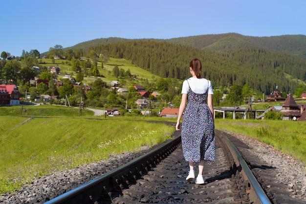 Młoda kobieta idzie wzdłuż torów kolejowych.