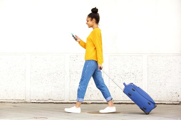 Młoda kobieta idzie z torba podróżna i przy użyciu telefonu komórkowego