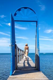 Młoda kobieta idzie za niebieskimi drzwiami na drewnianym chodniku na karaibskiej wyspie roatan w hondurasie
