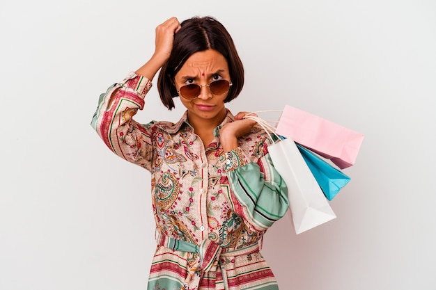 Młoda kobieta indian na zakupy niektóre ubrania na białym tle będąc w szoku, przypomniała sobie ważne spotkanie.