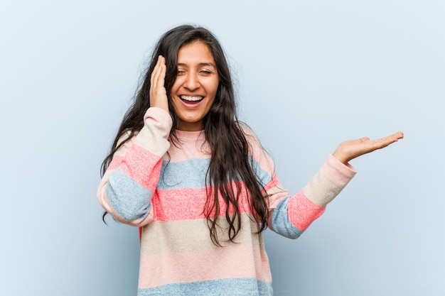 Młoda kobieta indyjska moda posiada miejsce na dłoni, trzymać rękę na policzku. zaskoczony i zachwycony.
