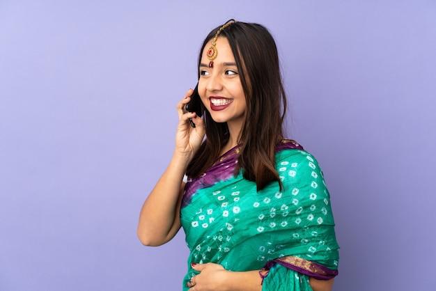 Młoda kobieta indyjska na fioletowe ściany prowadzenie rozmowy z telefonem komórkowym