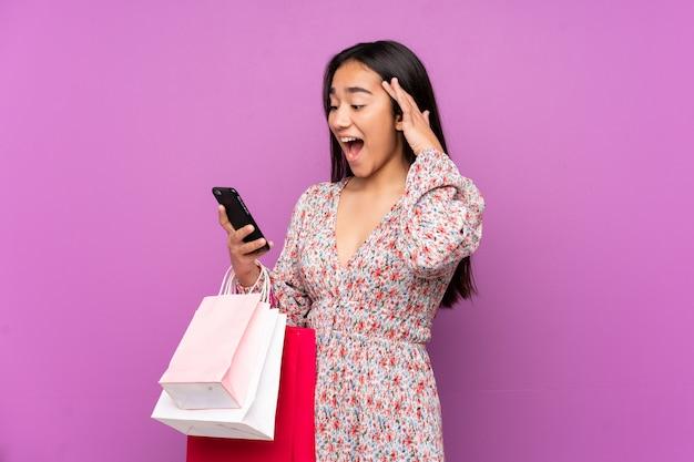 Młoda kobieta indyjska na fioletowe ściany, trzymając torby na zakupy i pisząc znajomemu telefon komórkowy