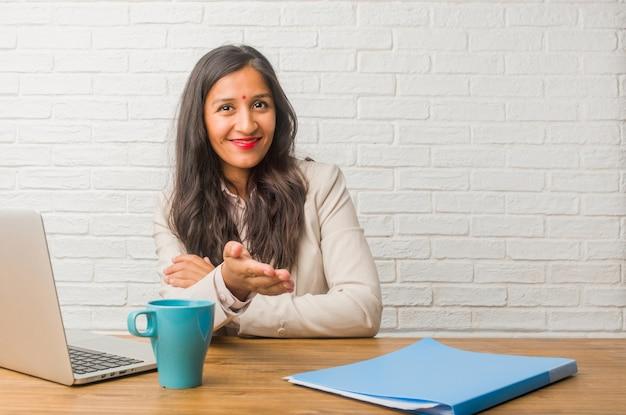 Młoda kobieta indyjska w biurze, która wychodzi na powitanie kogoś lub gestykuluje, aby pomóc