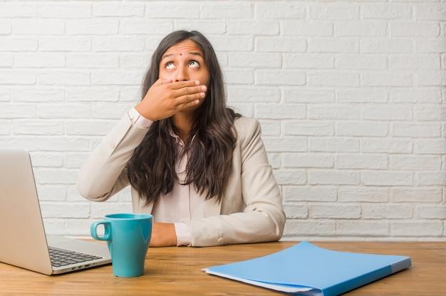 Młoda kobieta indyjska w biurze obejmujące usta, symbol ciszy i represji, starając się nic nie mówić