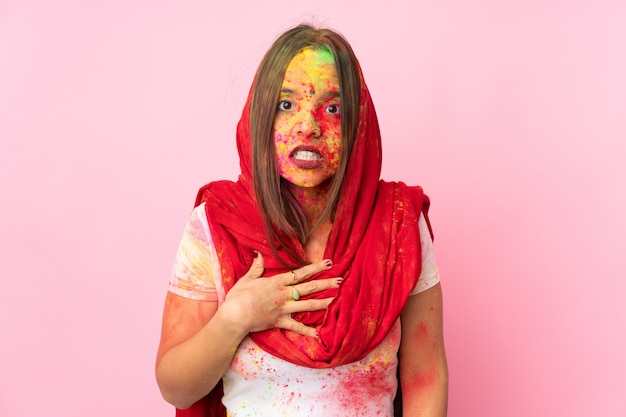 Młoda kobieta indyjska z kolorowymi holi w proszku na twarzy na różowej ścianie, wskazując na siebie