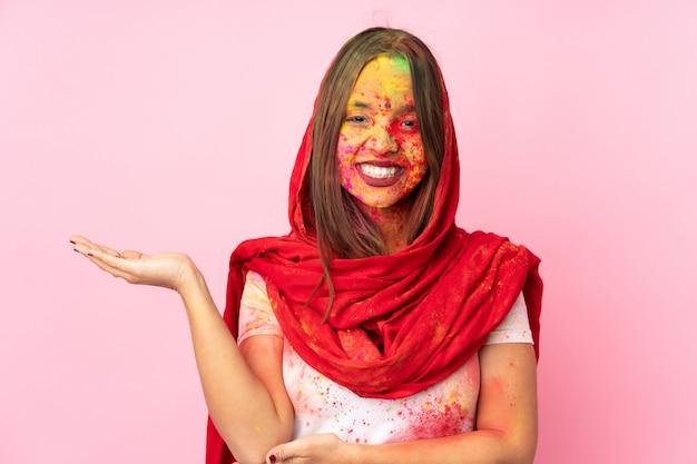 Młoda kobieta indyjska z kolorowymi proszkami holi na twarzy na różowej ścianie, mająca wątpliwości
