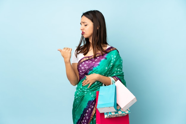Młoda kobieta indyjska z torby na zakupy niezadowolony i wskazując na bok