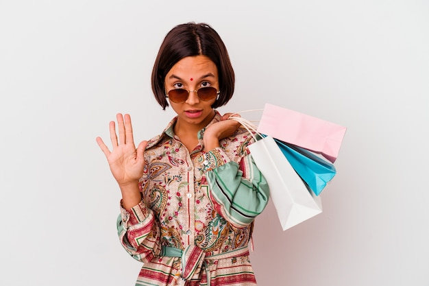Młoda kobieta indyjska zakupy niektóre ubrania na białym tle stojąc z wyciągniętą ręką pokazując znak stop, uniemożliwiając.