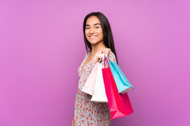Młoda kobieta indyjskich na białym tle na fioletowym tle trzymając torby na zakupy i uśmiechnięty
