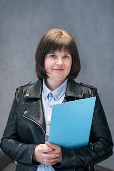 Młoda kobieta inspektor w skórzanej kurtce z dokumentami w ręce. nowoczesna biznesowa kobieta. nieformalne przyjęcie