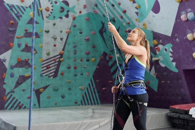 Młoda kobieta instruktor wspinaczki trzymając linę bezpieczeństwa, stojąc przy ścianie ze skałami i patrząc w górę