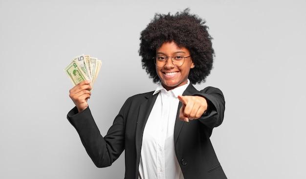 Młoda kobieta interesu afro, wskazując na aparat z zadowolonym, pewnym siebie, przyjaznym uśmiechem, wybierając ciebie. pomysł na biznes
